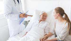 medicine, healthcare and people concept - senior woman patient with daughter and doctor with clipboard at hospital ward